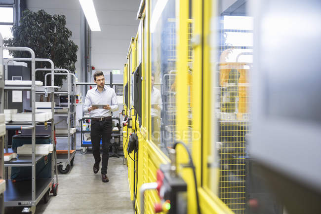 Молодой бизнесмен проверяет автоматизированное производство — стоковое фото