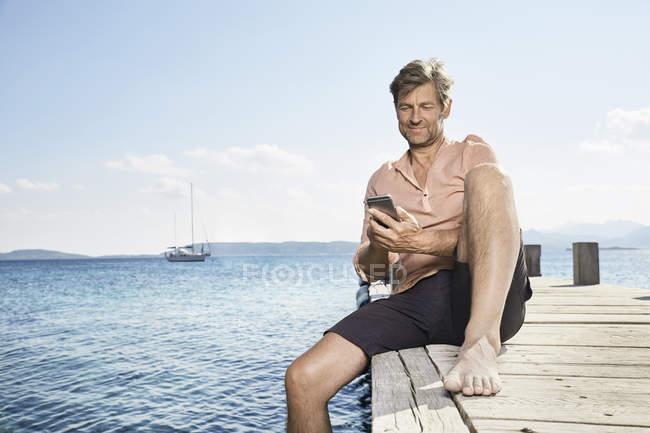Homem no cais, usando telefone celular — Fotografia de Stock