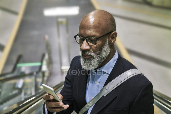 Businessman using smartphone on escalator — Stock Photo
