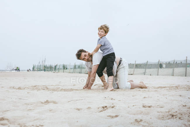Father and little son playing together on beach — Stock Photo