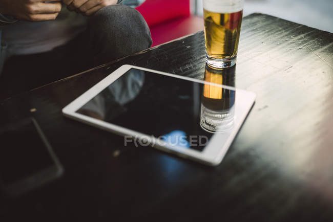 Digital tablet and glass of beer — Stock Photo