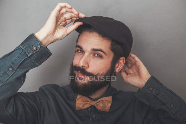Bearded man putting on cap — Stock Photo