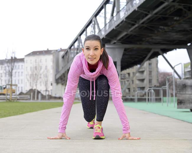 Женщина-легкоатлетка в стартовой позиции — стоковое фото