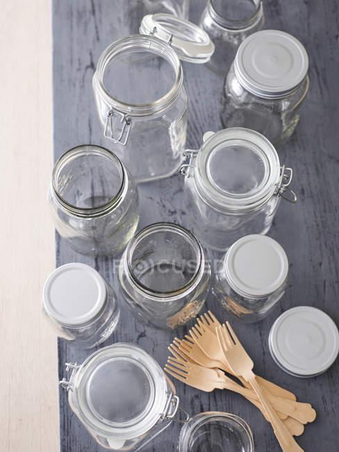 Vários frascos de conservas e garfos de madeira — Fotografia de Stock
