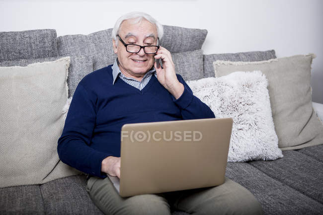 Senior man using laptop and smartphone — Stock Photo