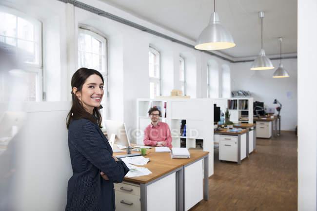 Femme souriante et homme au bureau — Photo de stock