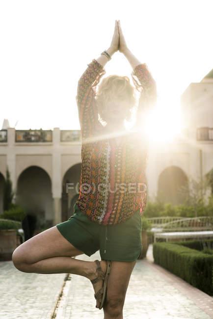 Female tourist doing yoga — Stock Photo