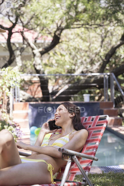 Woman on phone in deckchair — Stock Photo