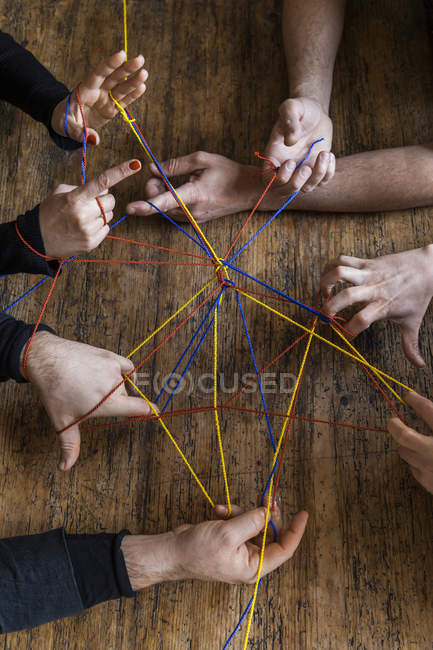 Cropped view of human hands holding colorful threads over wooden surface — Stock Photo