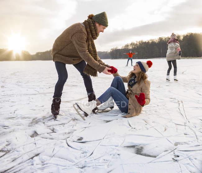 Человек, помогая льда катанию женщина вставать — стоковое фото