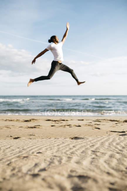 Homme sautant sur la plage — Photo de stock