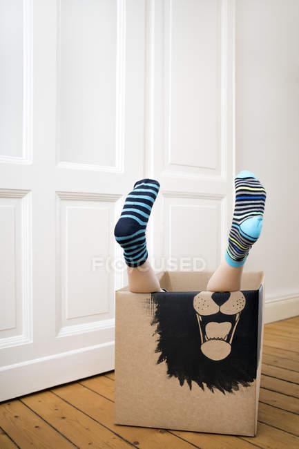 Ноги мальчика внутри картонной коробки — стоковое фото