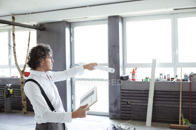 Architect with sketch book and construction plan — Stock Photo