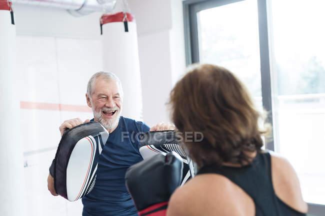 Ältere Frau mit Trainer Boxen — Stockfoto