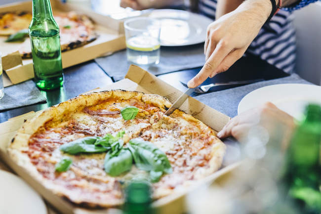 Hand cutting pizza — Stock Photo
