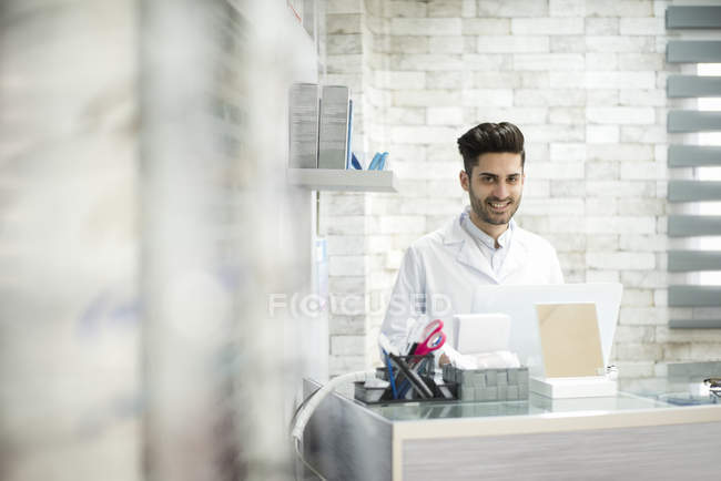 Optician sitting at table and looking at camera — Stock Photo
