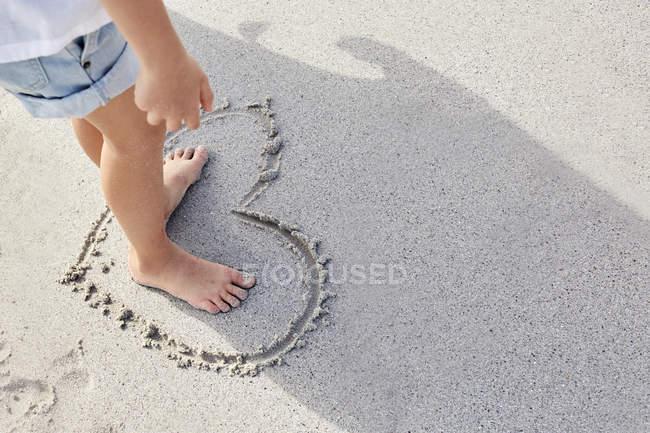Garota de pé na coração na areia — Fotografia de Stock