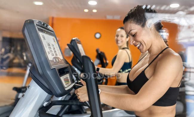 Women using elliptical trainers — Stock Photo