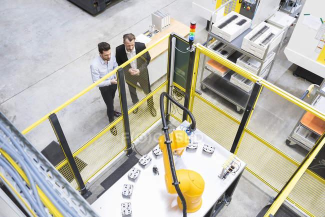 Dos empresarios observar robots industriales - foto de stock
