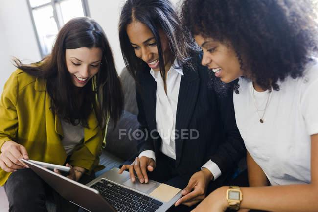 Empresárias compartilhamento portátil — Fotografia de Stock
