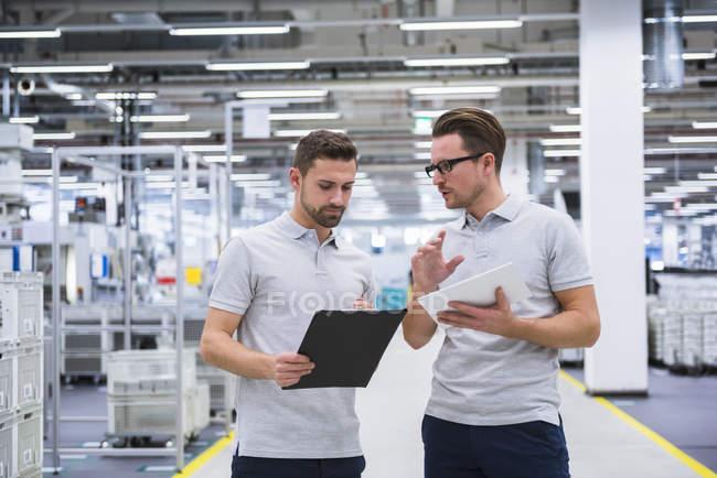 Two men talking in factory — Stock Photo