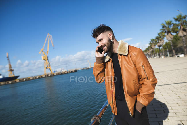 Young man at harbour talking on phone — Stock Photo