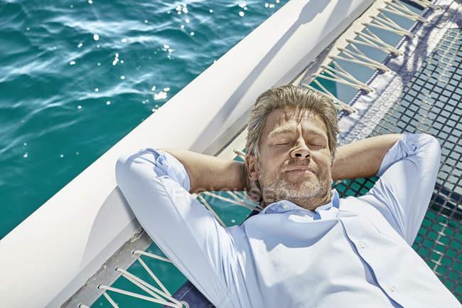 Homme couché sur un voilier — Photo de stock