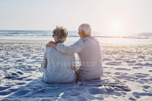Coppia anziana seduta sulla spiaggia — Foto stock