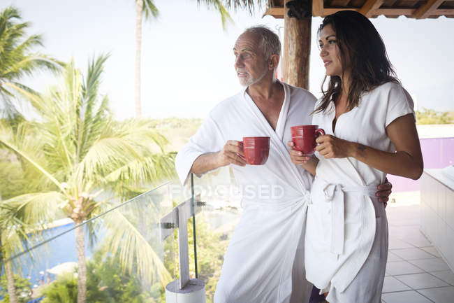 Mujer joven y hombre mayor con café en albornoces en el balcón - foto de stock