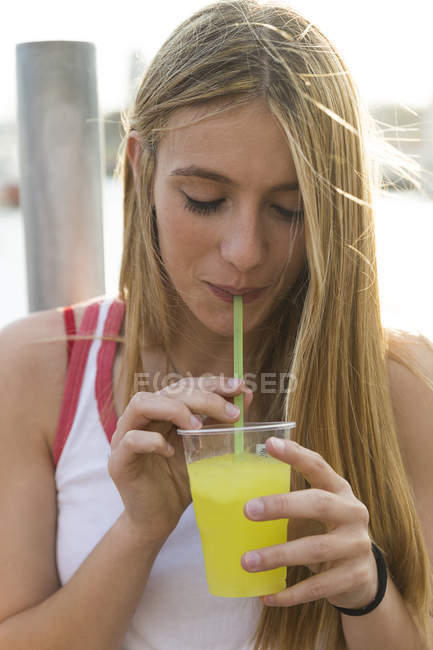 Woman drinking yellow beverage — Stock Photo