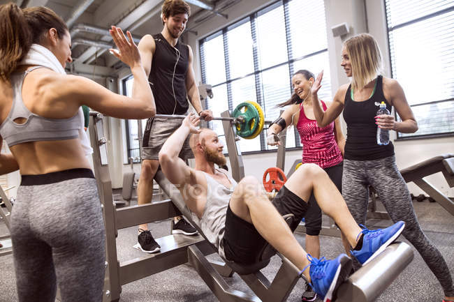 People in gym training weight lifting — Stock Photo