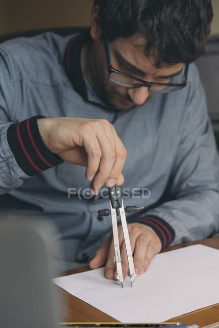 Young man using compasses at desk — Stock Photo