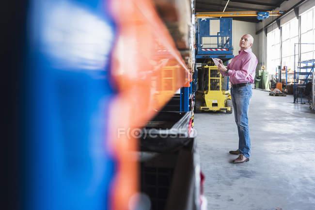 Человек с планшетом в индустриальном зале — стоковое фото