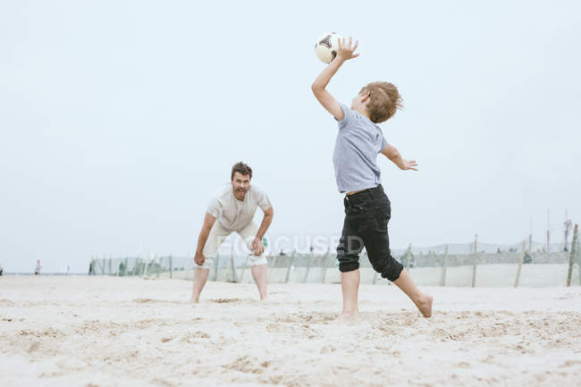 Father and little son playing with ball on beach — Stock Photo
