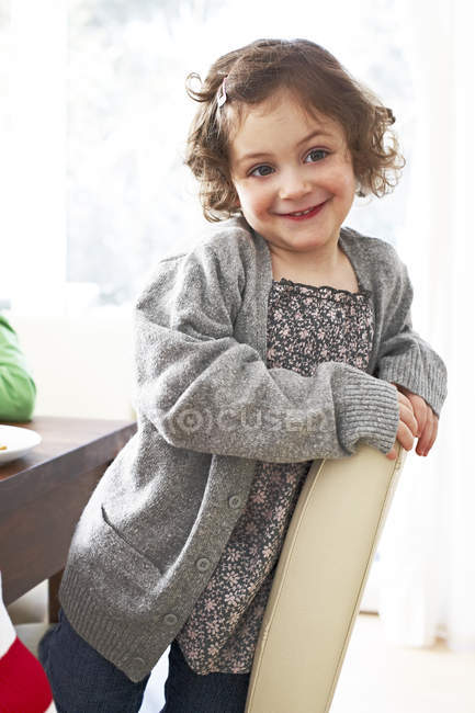 Girl kneeling on a chair at home — Stock Photo