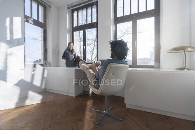 Casal sorridente, sentada na sala de — Fotografia de Stock