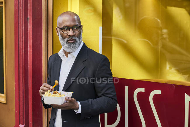Businessman eating French fries — Stock Photo
