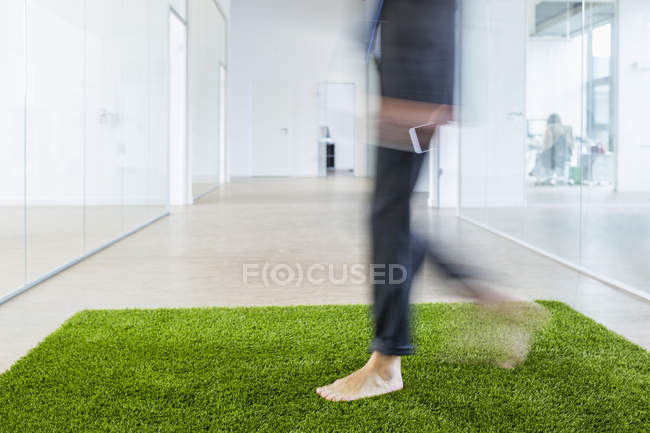 Businessman walking on grass carpet — Stock Photo