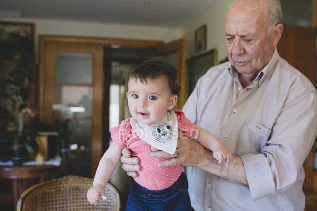 Babymädchen mit Ur-Großvater zu Hause — Stockfoto
