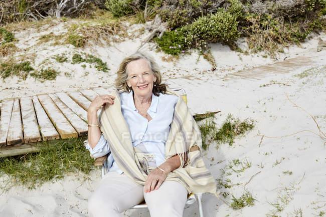 Жінка, сидячи на пляжі — стокове фото