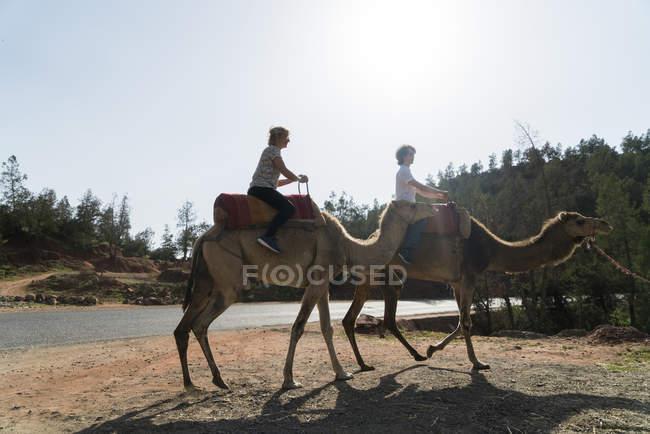Marocco, uomo e donna Equitazione cammello — Foto stock
