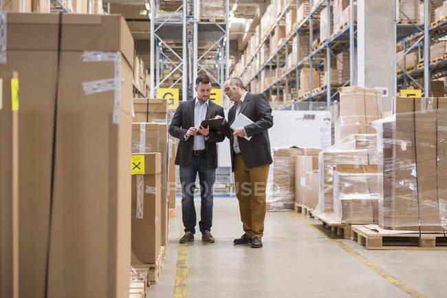 Deux hommes parlant dans l'entrepôt de l'usine — Photo de stock