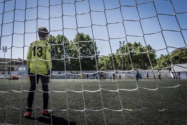 Boy as soccer goalkeeper standing at the gates — Stock Photo