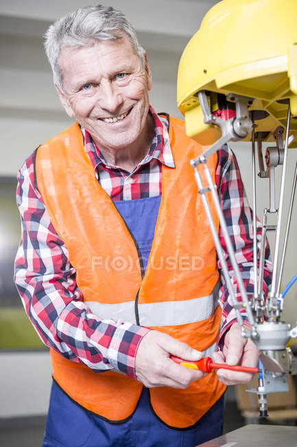 Portrait of smiling technician adjusting industrial robot — Stock Photo