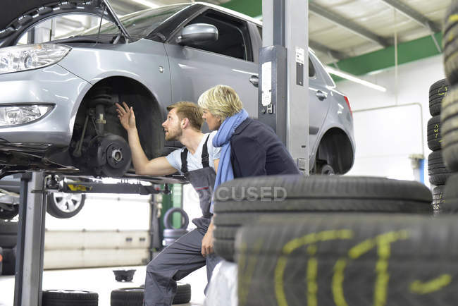 Car mechanic standing with client — Stock Photo
