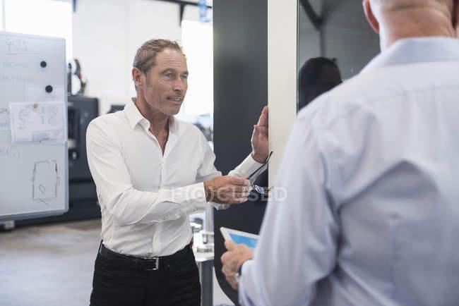 Men interacting on factory shop floor — Stock Photo