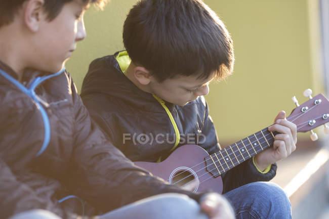 Boy playing ukulele — Stock Photo