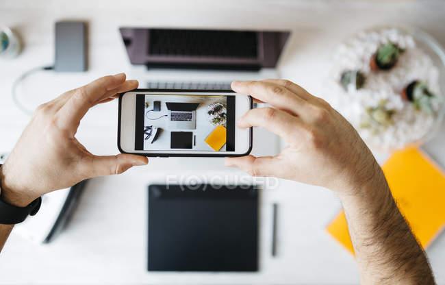Homme prend une photo de son ordinateur de bureau — Photo de stock
