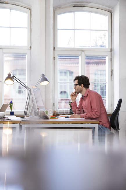 Man sitting at desk — Stock Photo