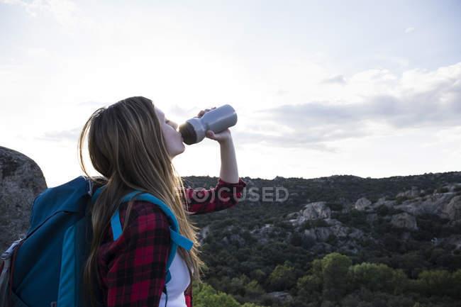 Donna che beve acqua durante il trekking — Foto stock